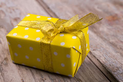 Little yellow gift with gold ribbon. Stock Photos