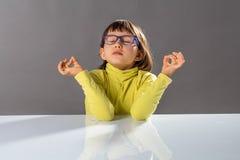 Zen little yoga child breathing, practicing yoga and closing eyes. Little yoga child with eyeglasses breathing, practicing yoga and closing eyes with inner Stock Images