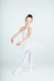 Little  young ballerina poses on camera. Little adorable young ballerina in white tutu poses on camera Stock Image