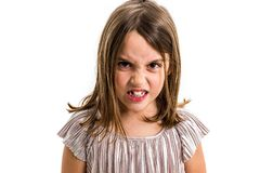 Little young girl is angry, mad, disobedient with bad behaviour. Children making the act of insubordination and disobedience, yelling, showing teeth, behaving stock photos