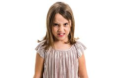 Little young girl is angry, mad, disobedient with bad behaviour. Children making the act of insubordination and disobedience, yelling, showing teeth, behaving stock image