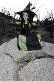 Little young girl costumed as witch sitting on rock looking away Royalty Free Stock Image