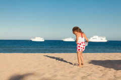 Little young girl searching in sea sand Royalty Free Stock Photo
