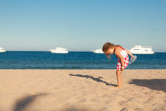 Little young girl searching in sea sand Stock Photography