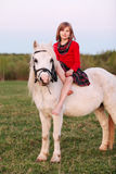 Little young girl sitting astride a white horse and smiling royalty free stock photography