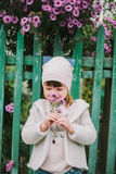 Little young girl sniffs a flower. on a background of green fe Royalty Free Stock Photo