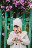 Little young girl sniffs a flower. on a background of green fe Royalty Free Stock Photos
