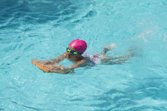 Little Young Girl Swimming in a  Pool Royalty Free Stock Photos