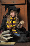 Little young witch with black cat and books Royalty Free Stock Image