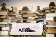 Little young woman sleeping on an open book Royalty Free Stock Images