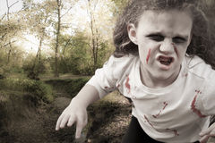 Little Zombie Girl Attacks. A little zombie girl looks like she is jumping out of the forest at you; woods and stream in the background; horizontal format, muted stock photography