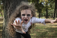 Little Zombie Girl. A little girl is dressed as a Zombie with scary makeup, blood stained clothing, and messy hair royalty free stock photo