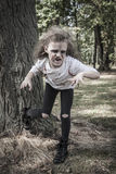 Little Zombie Girl. A little girl is dressed as a Zombie with scary makeup, blood stained clothing, and messy hair royalty free stock images