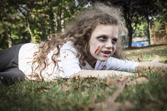 Little Zombie Girl. A little girl is dressed as a Zombie with scary makeup, blood stained clothing, and messy hair stock photos