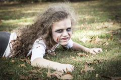 Little Zombie Girl. A little girl is dressed as a Zombie with scary makeup, blood stained clothing, and messy hair royalty free stock photos