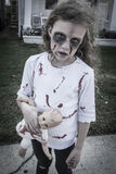 Little Zombie Girl. A little girl is dressed as a Zombie with scary makeup, blood stained clothing, and messy hair royalty free stock image