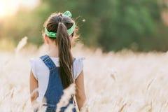 Littlegirl standing alone at the field during beautiful sunset. Children standing alone at the field during beautiful sunset stock photos