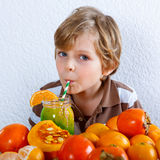 Littlke kid boy drinking healthy smoothie. Cute little preschool kid boy drinking fresh healthy organic smoothie. Healthy meal and drink. Orange fruits and royalty free stock photography