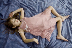 Littlle cute girl lying on the bed Stock Photography