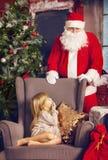 Littlle förvånade flickan och Santa Claus som ser henne Fotografering för Bildbyråer