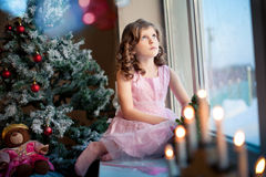 Littlle girl dreaming near Christmas tree Royalty Free Stock Image