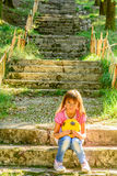 Littlle girl sitting on the stairs in the park. Littlle girl is sitting on the stairs in the park stock images
