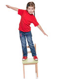Littlr gitl standing on a chair and balancing. On white Stock Photos