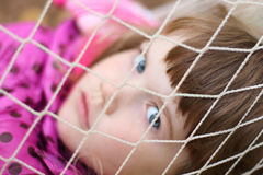 Littlt cute girl looks through white grid hammock Stock Image