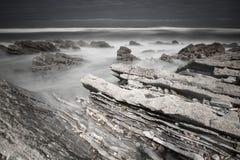 Littoral atlantique scénique avec des vagues dans le mouvement autour des roches sur la plage sablonneuse dans la longue expositi images libres de droits