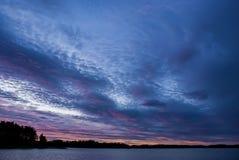 Littoral avec le ciel nuageux dans le lever de soleil pourpré Image stock
