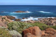 Littoral coloré près de Yallingup, Australie occidentale, avec les roches rouges, les buissons verts et l'océan profond-bleu photo stock