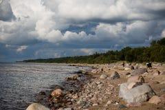 Littoral pierreux avec des nuages noirs photos stock