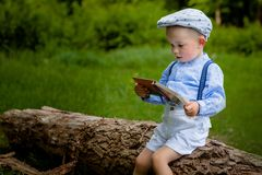 A litttle two year old Boy Sitting on a tree and Reads a Book. hildren Day Royalty Free Stock Photography