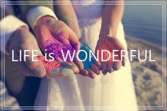 Liv är underbart över händer med många färger Arkivbild