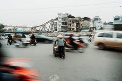 Liv av den vietnamesiska försäljaren i HANOI, VIETNAM Försäljaren försökte att korsa vägarna i galen trafik royaltyfri fotografi