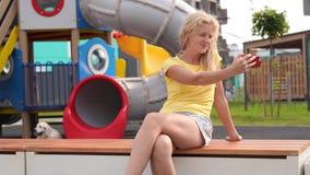 Liv i en modern stad - flickan med lockigt hår i tillfällig kläder sitter på en bänk nära lekplatsen med en smartphone arkivfilmer
