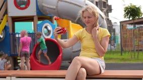 Liv i en modern stad - flickan med lockigt hår i tillfällig kläder sitter på en bänk nära lekplatsen med en smartphone lager videofilmer