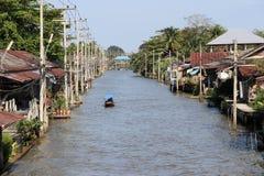 Liv längs fartygkörningen för kanal och för lång svans på den Damnoensaduak kanalen royaltyfri foto