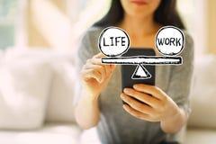 Liv- och arbetsjämvikt med kvinnan som använder en smartphone arkivbilder
