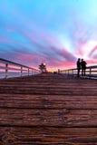 Liv som händer på pir i San Clemente under rosa färger och turkoshimmel Royaltyfri Foto