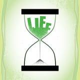 Livbegrepp med timglas och minskande sand på den texturerade gröna bakgrunden Royaltyfri Fotografi