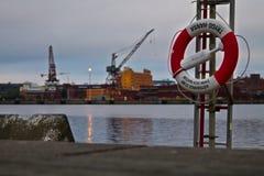 Livboj i hamn Räddningsaktioncirkel i hamn på natten Begrepp av säkerhet mot drunkningolyckor arkivfoto