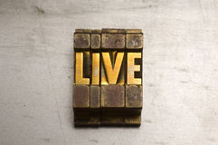 Live. Brass / Gold colored letterpress piece on silver metal background royalty free stock photography