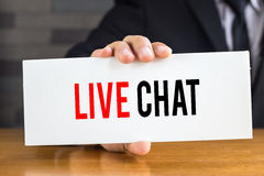 Live chat, message on white card and hold by Stock Photo