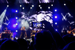 Live concert. Young fan with arm up and smartphone in the hand to record the event Royalty Free Stock Image