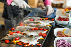 Live cooking. Chef preparing fish with vegetables. Live cooking on restaurant Stock Photography