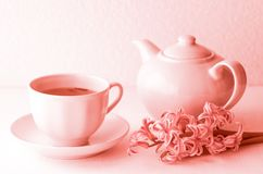 Live coral color is a composition of a teapot and a cup of tea. Fragrant hyacinth stock photo