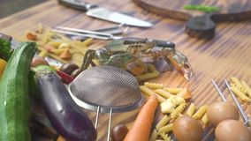 Live crab crawling on macaroni on vegetable background. Fresh ingredient for cooking seafood pasta in italian restaurant stock footage