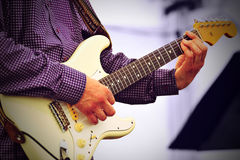Live guitar player. Old guitar player performing live on stage royalty free stock photo