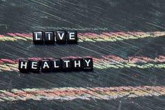 Live Healthy op houten blokken Kruis verwerkt beeld met bordachtergrond stock foto's